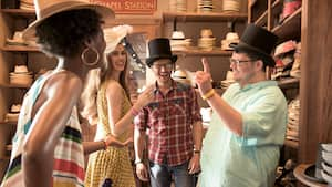 2 men and 2 women smile while wearing antique hats
