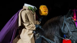 The headless horseman, dressed in overcoat, scarf and cape, sits atop his mount holding a carved jack o lantern in his left hand