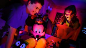 Two kids happily open glowing gifts in their hotel room, including a large, plush Halloween Mickey