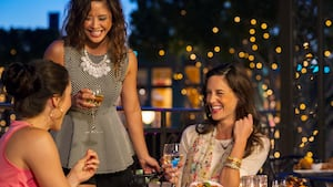 3 women laugh as they drink at a table