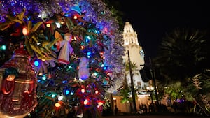 A Christmas tree near palm trees and Carthay Circle Restaurant