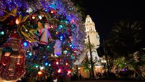 A Christmas tree near palm trees and Carthay Circle Restaurant