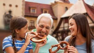 El abuelo muerde con placer un gran pretzel que le ofrece su nieta, mientras la hermana mayor ríe.