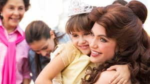 A little girl wearing a tiara smiles as she is hugged by Belle.