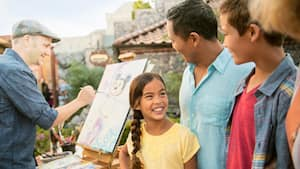 A smiling family stands near a man painting an image of Mickey Mouse