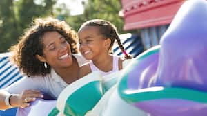 A mom and daughter smiling together while enjoying Dumbo the Flying Elephant at Magic Kingdom park