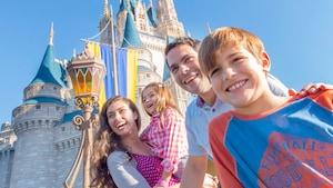 A family of 4 stands outside Cinderella Castle in Magic Kingdom Park at Walt Disney World Resort
