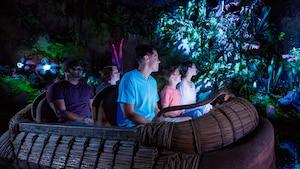 Visitantes apreciam os efeitos bioluminescentes da Na'vi River Journey a bordo de um bote trançado