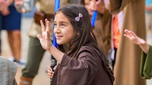 Una niña vestida con una bata de Jedi sujeta un sable de luz de juguete en su mano derecha mientras levanta la mano izquierda