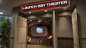 A screen with a logo reading Star Wars Launch Bay and some of the seats of the theater are framed by open side doors above which is a sign with the words Launch Bay Theatre and letter like characters reminiscent of an alien alphabet