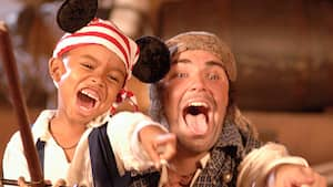 A young boy dressed as a pirate and wearing pirate themed Mickey ears points and playfully growls with Jack Sparrow's shipmate Mack