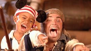 Un niño vestido como un pirata y usando orejas de Mickey con temática de piratas señala y gruñe alegremente con el compañero de barco de Jack Sparrow