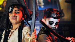 Niño y niña piratas esgrimen espadas