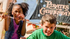 A young girl and boy growl and strike intimidating pirate poses in front of the Pirates of the Caribbean attraction