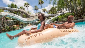 A father and daughter floating in a pool on a large inflatable raft