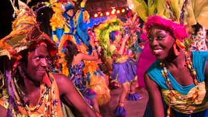 Male and female Discovery Island Carnivale performers dance at night at Disney's Animal Kingdom park