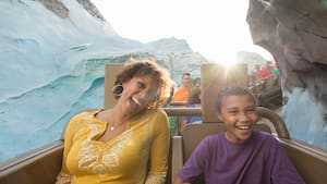 A mother and her son smile while riding aboard Expedition Everest - Legend of the Forbidden Mountain