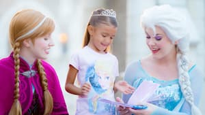 A female Guest enjoys a Character Greeting experience with Anna & Elsa at the Norway Pavilion at Epcot
