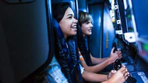 Jovens Visitantes seguram conjuntos de controles durante a Mission: SPACE no Future World no Epcot
