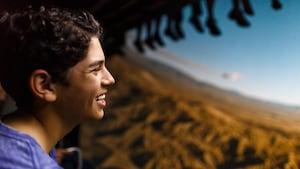 Jovem Visitante sorri curtindo a Soarin' Around the World no Future World do Epcot