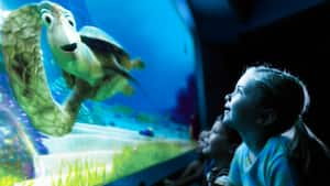 Una joven Visitante sonríe con entusiasmo mientras experimenta Turtle Talk with Crush en Future World