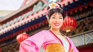 Mulan sorrindo no Pavilhão da China no Epcot, usando um colorido quimono chinês e flores nos cabelos