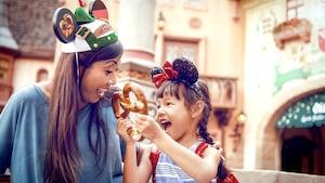 Una mujer sonríe con una niña que sostiene un pretzel