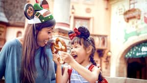A woman laughs with a girl holding a pretzel