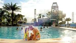A woman and a girl sit at the edge of a pool with a waterslide and swimmers
