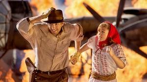 Indiana Jones y Marion corren desde un avión prendido fuego del espectáculo Indiana Jones Epic Stunt Spectacular