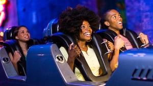 Um grupo de Visitantes sorri ansiosamente antes da partida na Rock 'n' Roller Coaster Starring Aerosmith