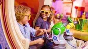 Un joven hermano y su hermana que llevan anteojos 3D sonríen mientras disfrutan a bordo de Toy Story Mania
