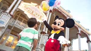 Mickey Mouse holding balloons while welcoming a Guest to Town Square Theater on Main Street, U.S.A.