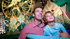 "A father and his son watch in wonder while riding aboard ""it's a small world"" at Magic Kingdom park"