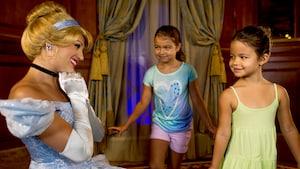 Cinderella sonríe elegantemente mientras saluda a 2 Huéspedes jóvenes dentro del Princess Fairytale Hall