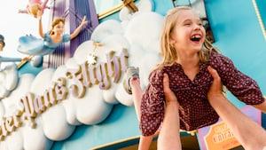 Uma jovem Visitante ri ao ser segurada no ar por seu pai perto da Peter Pan's Flight