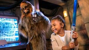 Una entusiasmada niña pequeña con un sable luminoso de juguete en un Encuentro con Personajes con Chewbacca