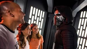 A mom and dad laugh as they meet Kylo Ren with their daughter during a Character Greeting experience