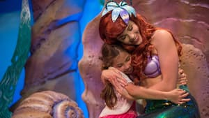 Ariel, the Little Mermaid, hugging a young girl
