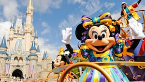 Minnie Mouse waves from a parade float in front of Cinderella Castle