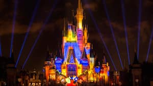 Vibrant lighting effects illuminate Cinderella Castle during Once Upon a Time at Magic Kingdom park