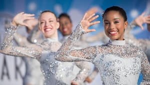 Teenage girls in sparkly sequined costumes hold their arms up during a dance routine
