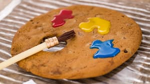 A cookie topped with blotches of frosting near an edible paint brush