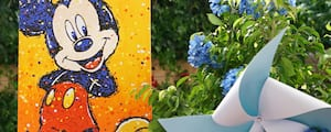 A painting of Mickey Mouse near flowers and a pinwheel