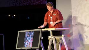 A man speaks on a stage and displays a picture of a woman painting