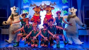 Performers dressed as Santa's elves pose with polar bears & reindeer Characters at Magic Kingdom park