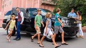 Un guía de excursión de Disney sostiene la puerta para que 4niños salgan de un SUV, mientras sus padres consultan un mapa del Parque