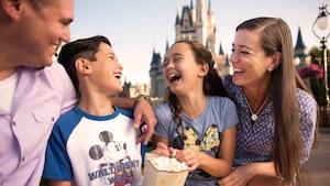 Un padre, una madre y su hijo e hija se ríen mientras comen palomitas de maíz cerca del Cinderella Castle