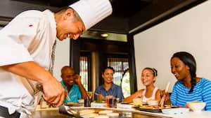 Excited Guests look on while an expert chef prepares an ornate dinner during the Hibachi Experience