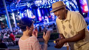 Un hombre y una mujer se sonríen emocionados mientras disfrutan de un concierto de ópera al aire libre